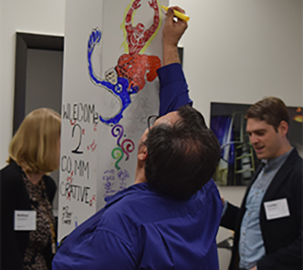 Guests at the Factory Mark grand opening having some fun drawing on one of the columns at CommCreative